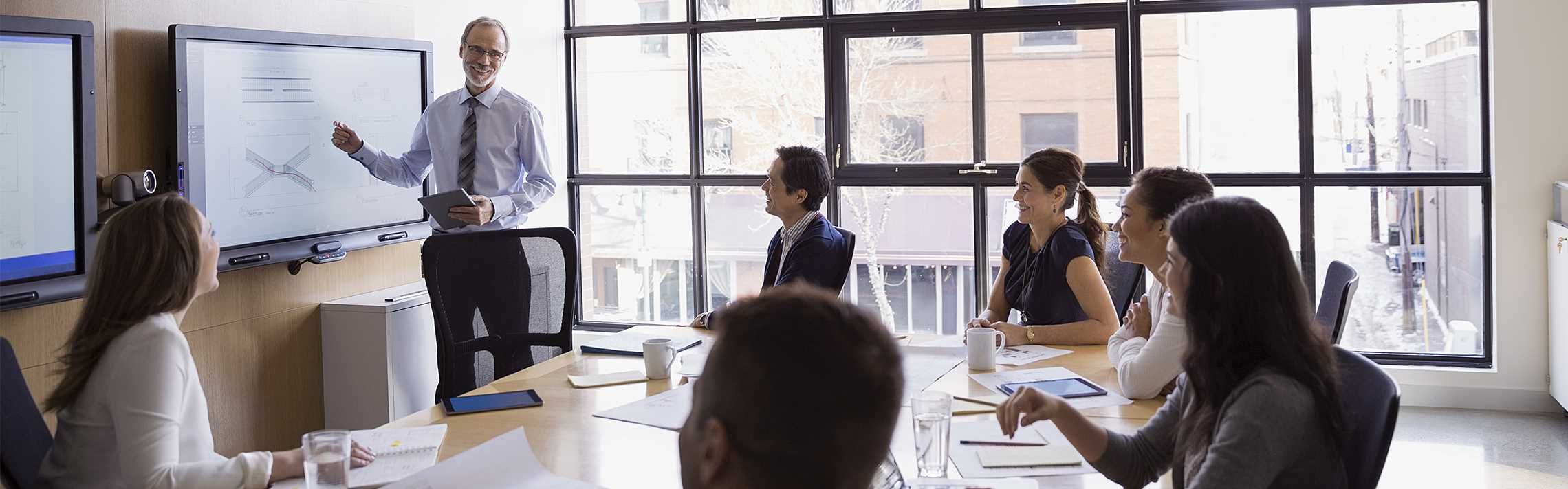 Businessman leading a meeting at a monitor in conference room.