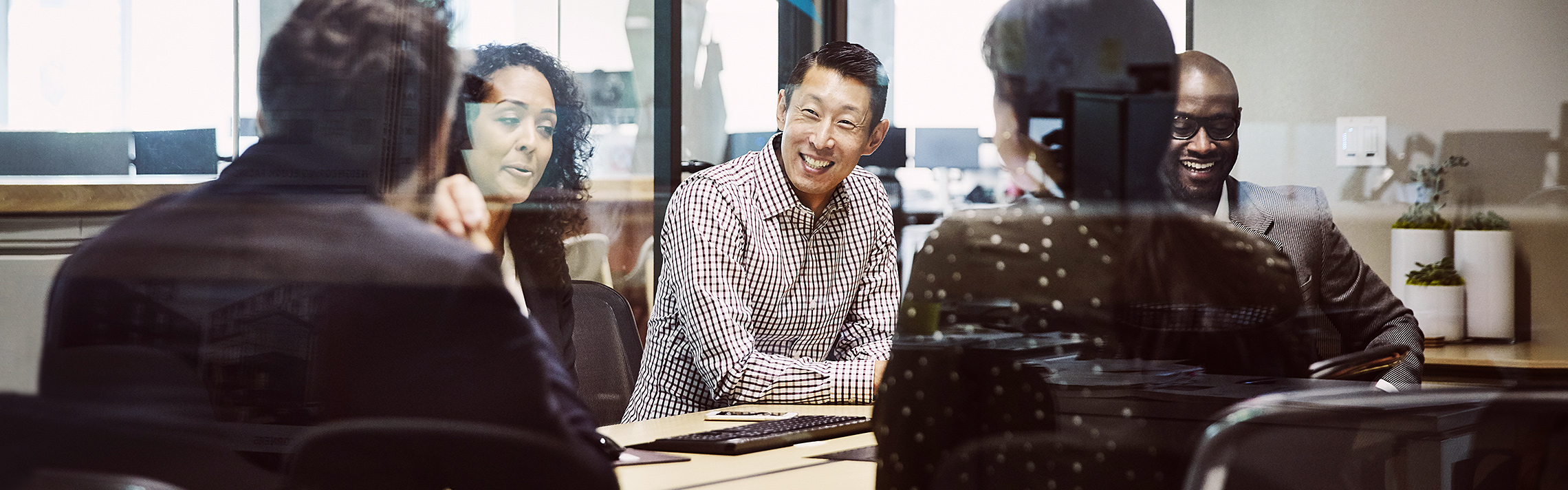 Smiling businessman leading client meeting in office conference room.